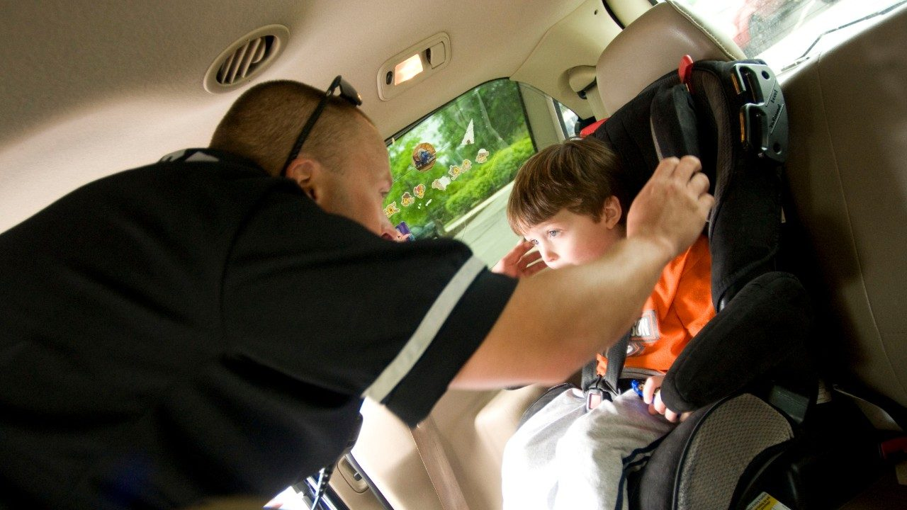 Police Officer Daniel Guilliams  checking a child seat