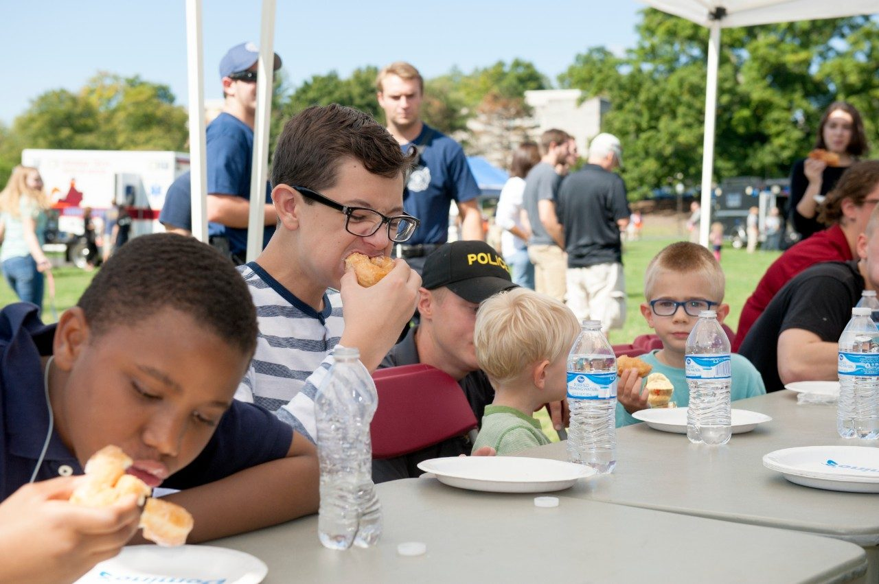Young participants eat doughnuts.
