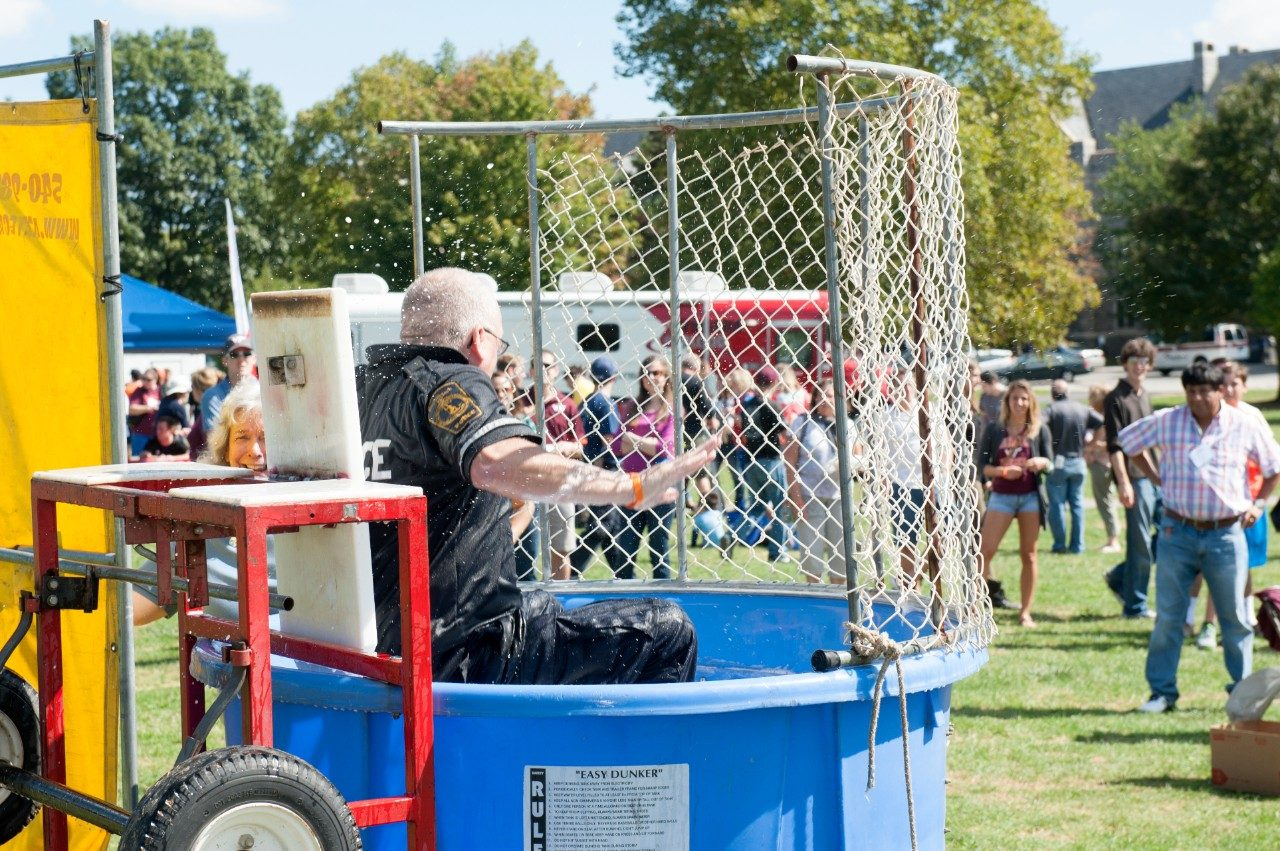 An officer falls into the dunk tank.