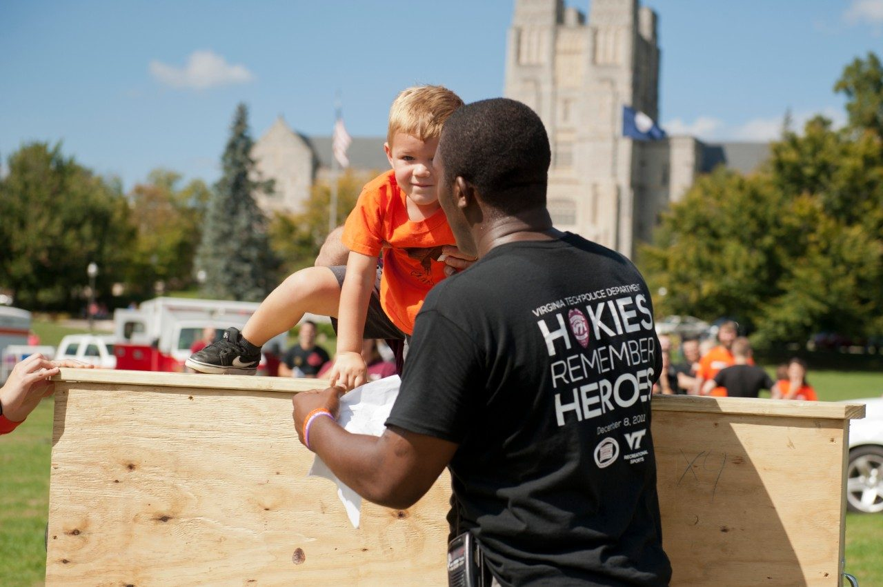 A young participant is assisted through the obstacle course.